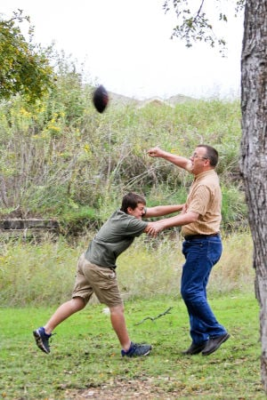Woods Family: Matthew Woods, 12, attempts to intercept the football while his dad, Bryan, throws it during a game in their yard.