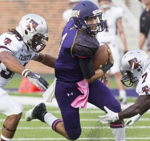 Trinity At UMHB: Mary Hardin-Baylor quarterback Zach Anderson carries ball between Trinity defenders Bradley Drenon, left, and Jamal Murray. - Josh Quinn | FME News Service