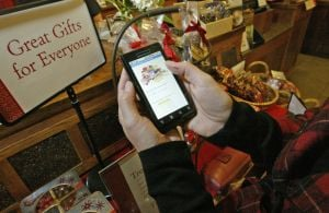 SMARTPHONE HOLIDAY SHOPPING: Shannon Titus plans to use a smartphone when shopping for the holidays as she scans some items on her phone at Peet's Coffee & Tea in Oakland, Calif. - Photo by Laura A. Oda | Bay Area News Group