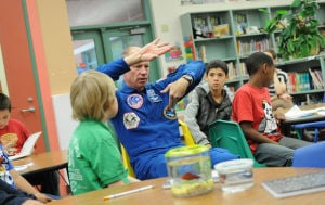 Astronaut At West Ward: Former NASA astronaut Richard Searfoss works with students Nov. 21 at West Ward Elementary School on designing microgravity experiments to go into suborbital flight. He is talking with students about a hypothesis regarding how fish might swim differently in low gravity. - Photo by TODD MARTIN | KISD
