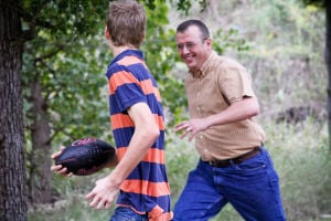 Woods Family: Jacob Woods carries the football while his dad, Bryan, chases him during a game of football in the yard.