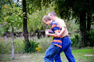 Woods Family: Jacob Woods, 14, laughs while his dad, Bryan, tackles him during a game of football in the yard.