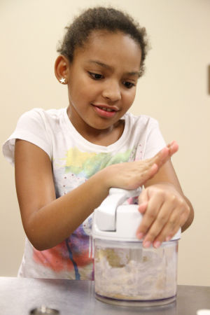Little And Blooming Chef's Academy: Emma Atterberry, 9, combines cookie ingredients during the Blooming Chefs Academy cooking class Monday afternoon at the Harker Heights Activites Center. - Herald/MARIANNE GISH