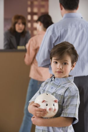 Boy with piggy bank waiting in line at bank