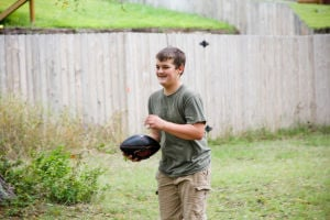 Woods Family: Mathew Woods, 12, prepares to throw the football during a game with his dad and brother.