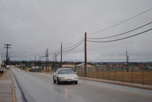 <p>A car drives on a wet Florence Road on Tuesday morning in Killeen.</p>