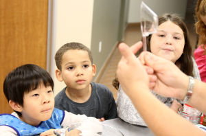 Little And Blooming Chef's Academy: Carly Ross, right, shows Aiden Lee, 5, left, Trey Atterberry, 6, middle, and Brooke Ross, 8, right, a measuring cup they need for their recipe during the Blooming Chefs Academy cooking class Monday afternoon at the Harker Heights Activities Center. - Herald/MARIANNE GISH