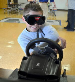 <p>Ely Purcell, 13, of Crossroads High School, loses control of his peripheral vision during a driving test that simulates nighttime driving and his blood alcohol content two times over the legal limit Wednesday at the school.</p>