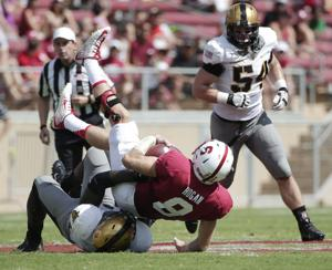 <p>Stanford quarterback Kevin Hogan is brought down by Army linebacker Andrew King during the first half of an NCAA college football game on Saturday, Sept. 13, 2014, in Stanford, Calif. </p>