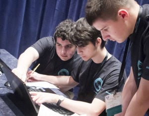 CYBER-CONTESTS: Marshall Academy team members Peter Marr, left, Xhesi Galanxhi, and Jacob Walters confer at the CyberPatriot contest at National Harbor, Md. in March. Cyber-contests are sprouting up around the country under the guidance of federal officials who are keen to boost their agencies' computer defense forces. - Brittany Gray | Air Force Association