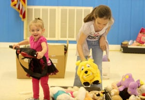 Kempner VFD Auction: Emma Mainville, 2, and her sister, Faith Mainville, 8, look over a selection of items up for auction during the Kempner Volunteer Fire Department fundraiser Saturday, March 1, 2014, at the Kempner Volunteer Fire Department. - Herald/CATRINA RAWSON