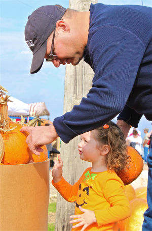 Walker Honey Farm: Temple resident John Merkel helps his daughter, Nora, 2, with her pumpkin at Walker Honey Farm on Saturday in Rogers during the Fall Farmers Market. - Photo by Steve Pettit | Herald