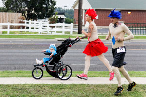 Monster Dash: Corinthia Barnhart pushes her 14-month-old son, Titus, in a stroller while running with her husband, Adam Barnhart, during the Monster Dash on Saturday morning. - Jodi Perry | Herald