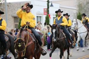 <p>Members of the Rough Riders club ride horses and wave to the crowd during the Killeen Christmas Parade,Dec. 13, 2014.</p>