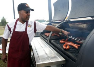 Octoberfest4.jpg: Kenneth Rhodes with Lucille's Bar-B-Que cooks sausages at the grill during the Oktoberfest event at Carl Levin Park in Harker Heights. - Photo by Jaime Villanueva