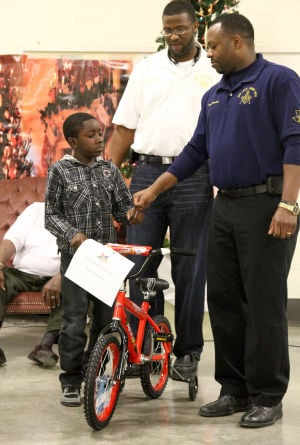 Bike Giveaway: De'Andre Williams, 8, fist pumps Pete Borders, the worshipful master, after De'Andre received a bike during the giveaway event hosted by the New Light Masonic Lodge No. 242 on Thursday, Dec. 19, 2013, at the National Guard Armory in Killeen. - Herald/MARIANNE GISH