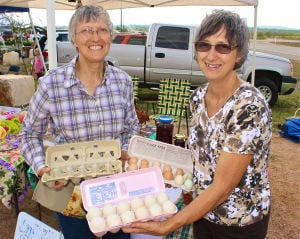 Walker Honey Farm: From left, Sandra Mikesell and her sister, Linda Hunter, had an assortment of fresh duck, chicken and quail eggs for sale in addition to homemade baked goods at Walker Honey Farm's Fall Farmers Market on Saturday in Rogers. - Photo by Steve Pettit | Herald