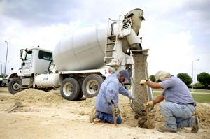 <p>Wallace Moody, left, and Hilario Ramirez, with David King Construction, help pour concrete at the construction site of the soon-to-be Nov. 5, 2009, Fort Hood Shooting Memorial on Thursday on South W.S. Young Drive in Killeen.</p>