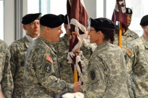 <p>Col. Patricia Darnauer, right, commander of Carl R. Darnall Army Medical Center, passes the Warrior Transition Unit's colors to incoming commander Col. Douglas Woodall on Thursday at Fort Hood.</p>