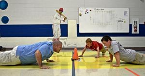 <p>Physical education teacher Michael Sheon motivates students to do correct pushups during class Wednesday, Sept. 24, 2014 at Fairview/Miss Jewell Elementary School.</p>