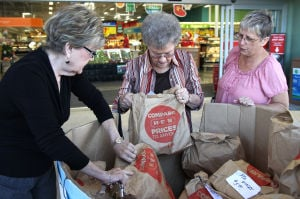 Holiday Hunger Help: Billie Pederson, middle left, Doris McCrary, director, middle, and Pat Moore, right, look at the Food for Families $5 brown paper bag donations by the Baptist Benevolence Association and H.E.B. on Tuesday, Nov. 19, 2013, at the H.E.B. in Copperas Cove. The food drive will be from 6 a.m. to 8 p.m. at the H.E.B. in Copperas Cove on Friday. - Herald/MARIANNE GISH