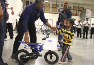 Bike Giveaway: Darryl Lardge III runs to his bike as Pete Borders, worshipful master, left, holds it during the bike giveaway event hosted by the New Light Masonic Lodge No. 242 on Thursday, Dec. 19, 2013, at the National Guard Armory in Killeen. - Photo by Herald/MARIANNE GISH