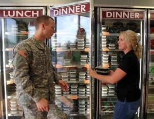 Living Here - Healthy Living: 2nd Lt. Carson Wren, 68th Engineer Company, 62nd Engineer Battalion, 36th Engineer Brigade, gets help picking out a Purefit Foods meal from Nancy Forester, a Purefit Foods sales representative, Thursday, November 14, 2013 at the restuarant in Killeen. - Herald/CATRINA RAWSON