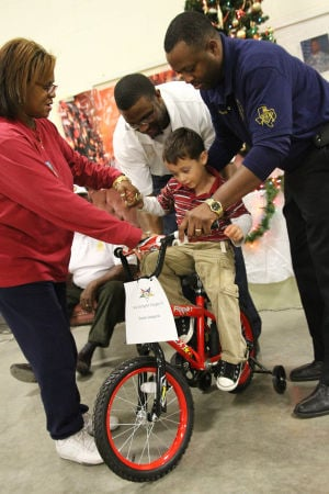 Bike Giveaway: Daven Lequeria sits on his new bike during the bike giveaway event hosted by the New Light Masonic Lodge No. 242 on Thursday, Dec. 19, 2013, at the National Guard Armory in Killeen. - Photo by Herald/MARIANNE GISH