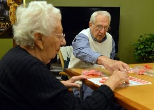 Long-term Care: Harry Baron, right, and his wife Claire play bingo at Arbor Terrace, an East Cobb assisted living community in Marietta, Ga., Nov. 20, 2013. Harry is still active, but his wife requires the assisted care of a nursing home. - Photo by Brant Sanderlin | Atlanta Journal-Constitution
