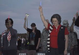 Veterans Day In Heights: Participants at the Harker Heights Veterans Day service hold glow sticks during a moment of silence Monday to honor those who gave the ultimate sacrifice. - Photo by Bryan Correira | Herald