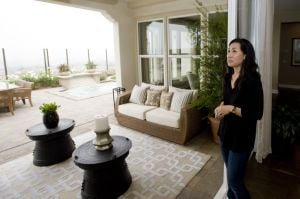 "Tips For Trade-up Homebuyers: Janet Son looks out onto a ""California Room,"" a covered deck with a fireplace and seating area in a model home identical to one she and her family purchased, a move-up from their smaller home in Brea, Calif. - Photo by Sam Gangwer 