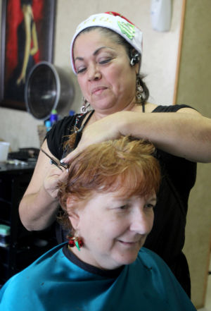 Podhorn Family Home: Maria Oliveras, owner of Maria's Beauty Salon, cuts the hair of Sarah Geiser of Copperas Cove, during the salon's 6th Annual Senior Citizen Party, Monday, December 16, 2013 in Copperas Cove. The party offered free haircuts, styles and manicures to all senior citizens. - Herald/CATRINA RAWSON