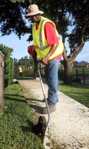Landscaping Business: Dennis Crutchen, with Central Texas Home and Lawn Transitions, trims the grass by the pavement in a yard Thursday morning on Stillwood Drive in Killeen. - Herald/MARIANNE LIJEWSKI