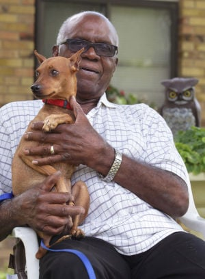 Lost Dog Found: Howard Lee poses on his front porch with Bandit, a 3-year-old miniature pinscher lost in Killeen four months ago and found in San Antonio last week. - Herald/Jaime Villanueva