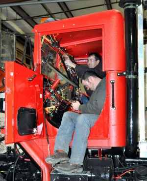 Fire Truck: Charles Compton, program manager for Kryish Government Group, and Kyle Simpson, mechanic, work on wiring for an M 939 being refurbished to become a fire pump truck. - Bryan Correira | Herald