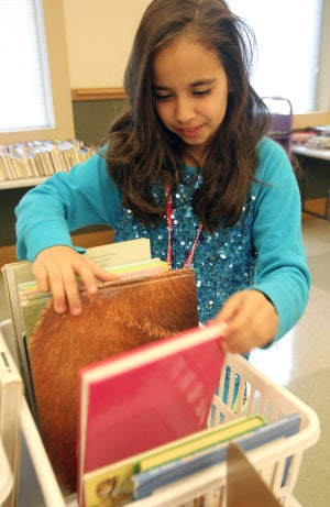 Harker Heights Book Sale: Megan Spano, 12, looks through a selection of books during a book sale Saturday at the Stewart C. Meyer Library in Harker Heights. Watch video at KDHnews.com. - Photo by Herald/CATRINA RAWSON