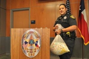 Police: A Copperas Cove police officer holds a bag of prescription drugs that were turned in to police Saturday. - Photo by Bryan Correira | Herald