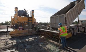 <p>A contractor with James Construction signals the driver of a concrete truck to dump his load into a slip-form Concrete paving machine working on new main lanes of Interstate 35 on Thursday morning near Belton. The efficent piece of equipment lays some 1,110 yards of concrete in just three hours time.</p>