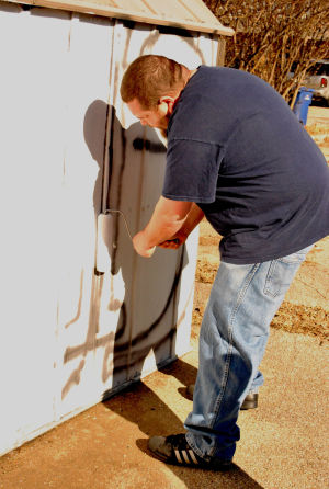 Graffiti: H-E-B volunteer Billy Cotter paints over graffiti on the side of a shed at Mighty Mart on Veterans Avenue on Tuesday. - Azeita Taylor | Herald