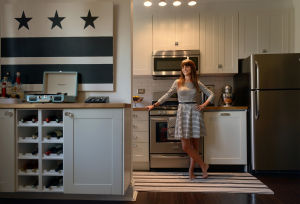 DESIGN-SMALL: Kiera Kushlan in the renovated kitchen of the 750-quare-foot co-op she shares with her husband Michael, who painted the black-and-white D.C. flag; the flag has been such a conversation piece it's now selling on Etsy. Illustrates DESIGN-SMALL (category l), by Jura Koncius (c) 2013, The Washington Post. Moved Thursday, September 19, 2013. (MUST CREDIT: Washington Post photo by BIll O'Leary.) - O'LEARY