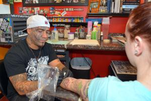 Artist touches up customer's tattoo