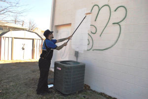 Graffiti: Copperas Cove Code Enforcement senior officer Beau Brabbin covers graffiti painted on a rear wall of the Mighty Mart on Veterans Avenue. - Azeita Taylor | Herald
