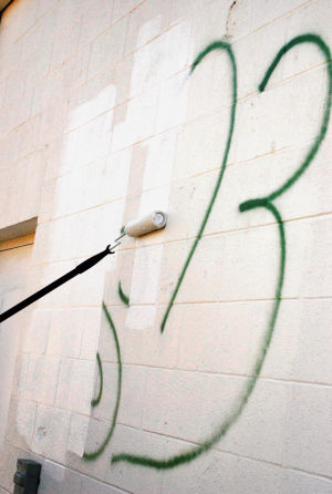 Graffiti: Copperas Cove Code Enforcement senior officer Beau Brabbin covers graffiti painted on a rear wall of the Mighty Mart on Veterans Avenue on Tuesday, Feb. 4, 2014. - Azeita Taylor | Herald