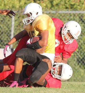 Future Stars Football: Smith Middle School's Shawn Gonzalez is wrapped up by Manor defenders during Tuesday's game at Manor Middle School. - Herald/CATRINA RAWSON
