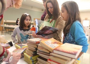 Harker Heights Book Sale:  Marissa Spano, 9, her mother, Deya Spano, and her sister, Megan Spano, 12, look through books during a sale Saturday at the Stewart C. Meyer Library in Harker Heights. - Photo by Herald/CATRINA RAWSON