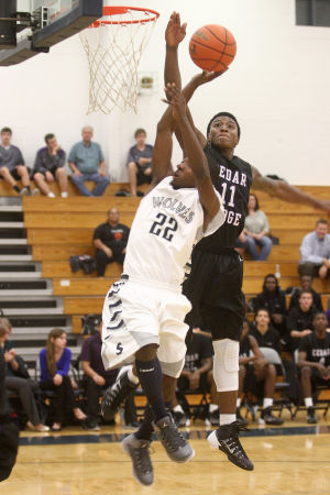 Boys Basketball: Shoemaker V. Cedar Ridge: Shoemaker's Tyrone Williams attempts a basket against Cedar Ridge's De'andre Davis Monday night at Shoemaker. - Herald/MARIANNE GISH