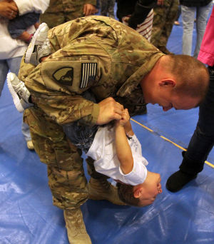 937th Route Clearance Company Homecoming: Spc. Landon Soper, 937th Route Clearance Company, 8th Engineer Battalion, 36th Engineer Brigade, dips his son, Gauge, 2, during a homecoming ceremony Monday, Nov. 4, 2013, at the West Fort Hood Physical Fitness Center. - Herald/CATRINA RAWSON