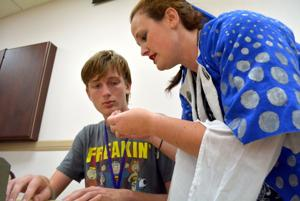<p>Sarah Vold shows Zackary Rokosh, 16, how to thread a needle Oct. 15 at the Medieval Arts and Sciences program at the Copperas Cove Public Library.</p>