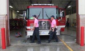Copperas Cove Firefighters Support Breast Cancer Awareness: Tyler Paulus and Trever Barclay both firefighters with the Copperas Cove Fire Department work on their fire truck while helping to support breast cancer awareness month by sporting a pink shirt, Wednesday, October 16, 2013 at the downtown Copperas Cove Fire Station. - Herald/CATRINA RAWSON