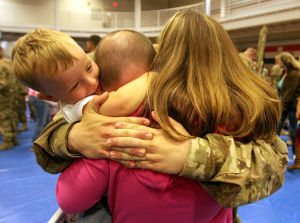 937th Route Clearance Company Homecoming: Spc. Landon Soper, 937th Route Clearance Company, 8th Engineer Battalion, 36th Engineer Brigade, hugs his son, Gauge, 2, and his wife, Chelsea Stokes, during a homecoming ceremony Monday, Nov. 4, 2013, at the West Fort Hood Physical Fitness Center. - Herald/CATRINA RAWSON